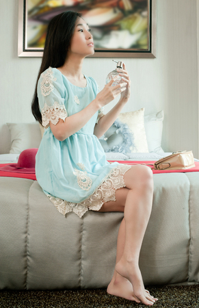 Elegant young beautiful asian woman holding bottle of perfume and applying on her neck in a room.