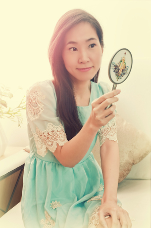 Asian woman looking in classical vintage silver mirror.
