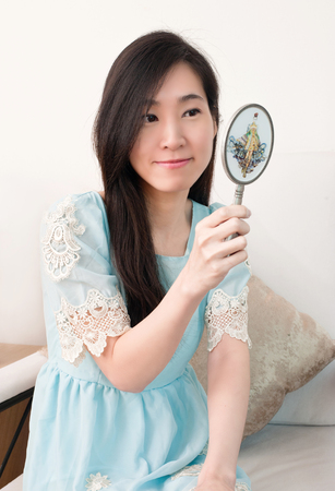 Asian woman holding and looking in classical vintage silver mirror.