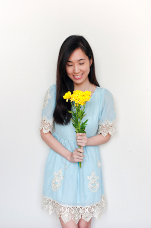 portrait of smilimg asian girl holding bouquet with yelliow flowers on white background. Stock Photo