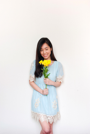 portrait of smilimg asian girl holding bouquet with yelliow flowers with copyspace.