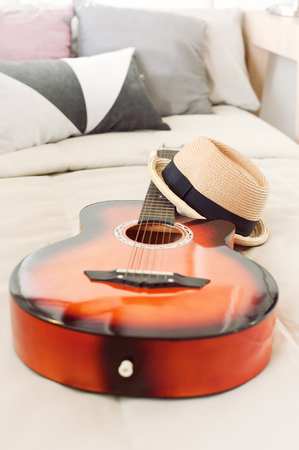 Stylish hipster hat laying on guitar in musician bed.shallow DOF.