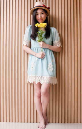 Full length portrait of smiling asian girl wearing hat and l holding bouquet with yellow flowers against wood wall. Stock Photo