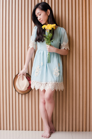 Full length portrait of smiling asian girl holding hat and bouquet of yellow flowers against wood wall.Woman feel happy while posing in fashion style. Stock Photo