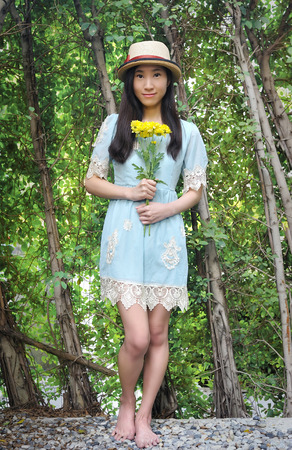 Full length portrait of asian girl holding bouquet of yelliow flowers against green plants wall background.
