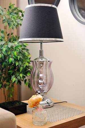Elegant metal desk lamp on wooden table. Stock Photo