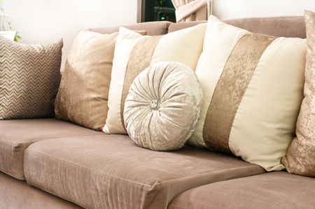 Decorative fabric cushion on light brown sofa.