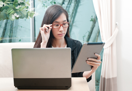 Business asian woman wearing eyeglasses work with tablet and laptop on wooden desk.