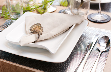 Napkin on the white plates and cutlery on decorated table setting. Stock Photo