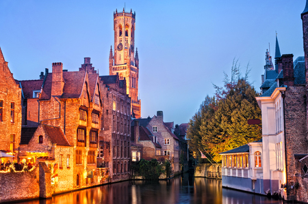 View of river canal and Belfort (Belfry) tower at twilight from Rozenhoedkaai,famous boat tour point in Bruges, Belgium.