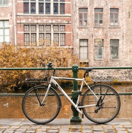 Bicycles standing near canal with European medieval building on a autumn day.