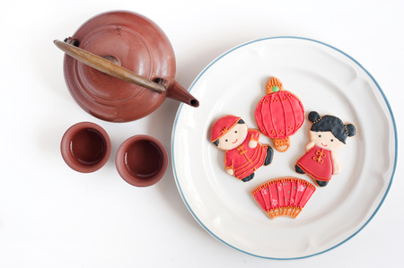 Top view of homemade gingerbread as Chinese boy and girl dolls in the white plate and tea pot on white background, for Chinese New Year and other festivals.