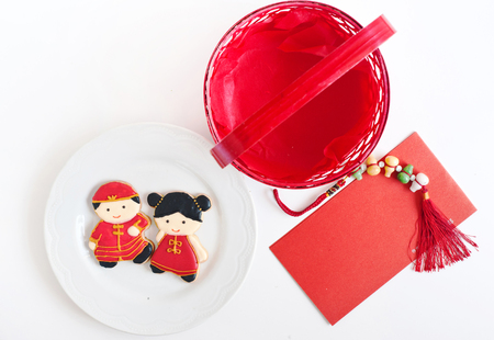 Homemade gingerbread as Chinese boy and girl dolls in the white plate and red envelopes for Chinese New Year on the white background.