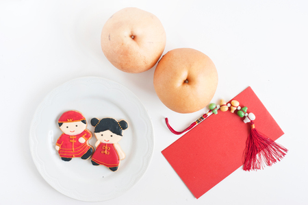 Homemade gingerbread as Chinese boy and girl dolls in the white plate, chinese pears and red envelopes for Chinese New Year on the white background. Stock Photo