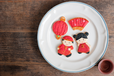 Top view of homemade gingerbread as Chinese boy and girl dolls in the white plate and a tea cup on old wood boards, For Chinese New Year and other festivals.
