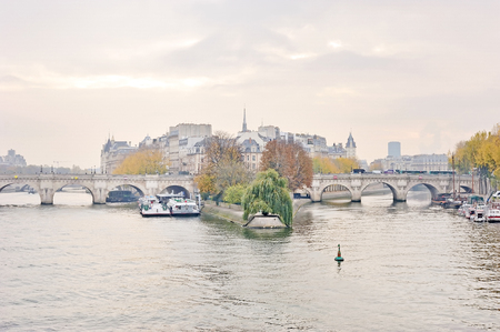 Panorama view of the Pont Neuf, bridge over the Seine in Paris, France in cloudy sky.