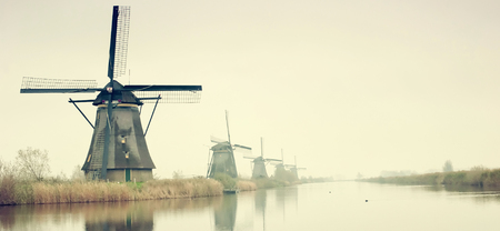 The Famous Netherlands wooden Windmills, Kinderdijk Windmill village in the soft sunset light of winter. 스톡 콘텐츠
