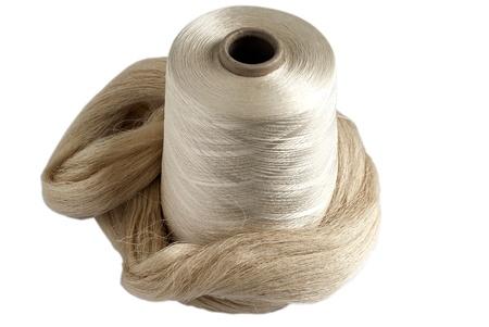 Silk yarn bobbin and raw silk skein isolated on white background