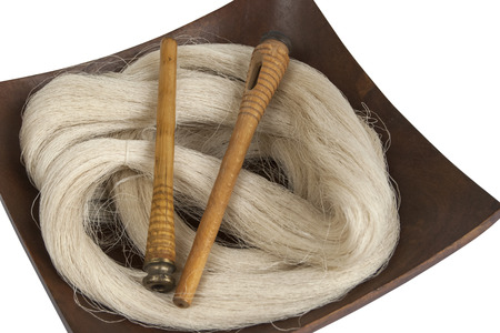 Raw silk yarn and spools of old loom in wooden platter