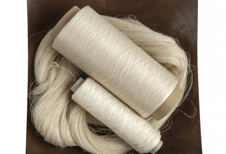Raw natural silk yarn skein and bobbins in wooden platter isolated on white background