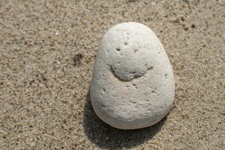 naturally: Naturally received image of smile on sea pebble stone on sand background