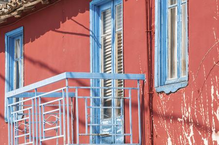 balcony door: Fachada de la casa roja con la puerta azul balc�n y ventanas
