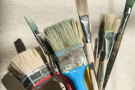 staining: Bunch of various used paintbrushes on canvas background Stock Photo