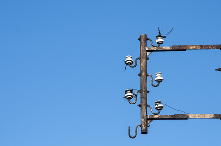 disuse: Disused isolators of street electric cables on metal frame on blue sky background