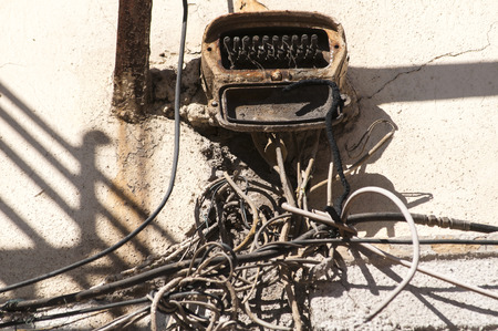 loopable: Tangle of old grunge obsolete cables left on old townhouse wall