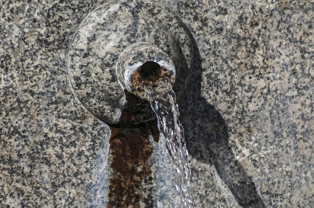 spout: Stone spout of fountain with gushing thermal mineral water Stock Photo