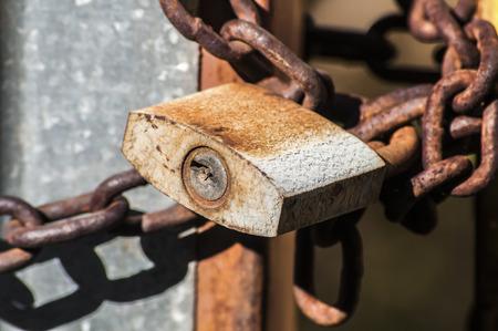 rusty chain: Weathered rusty grunge padlock and metal chain Stock Photo