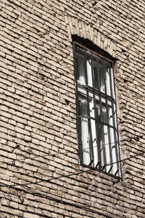 window bars: Window with bars on rear brick old house wall Stock Photo