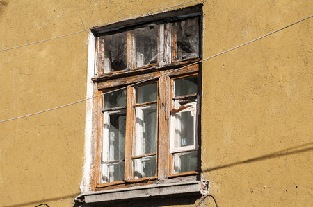 neglected: Old weathered grunge window of neglected abandoned townhouse facade Stock Photo