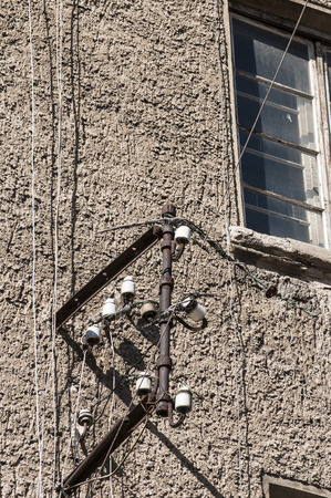 Old grunge metal frame with porcelain insulators for weathered electrical wires on facade of old town house