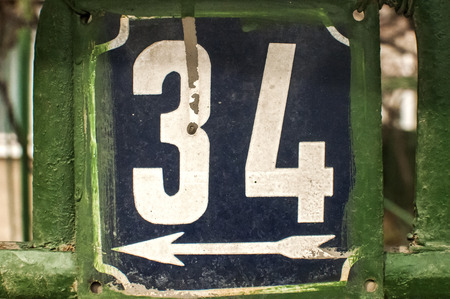 34: Weathered grunge square metal enameled plate of number of street address with number 34 closeup