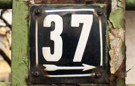 enameled: Weathered grunge square metal enameled plate of number of street address with number 37 closeup Stock Photo