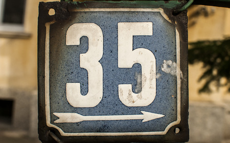 enameled: Weathered grunge square metal enameled plate of number of street address with number 35 closeup Stock Photo