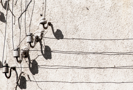 insulators: Old retro grunge street electric cables on porcelain insulators and their shadows on vintage house wall in sunny day resembling notes and musical staff