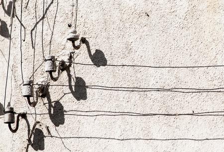 pentagrama musical: Vieja calle retro grunge cables el�ctricos en aisladores de porcelana y sus sombras sobre pared de la casa de la vendimia en d�a soleado notas asemejan y personal musical