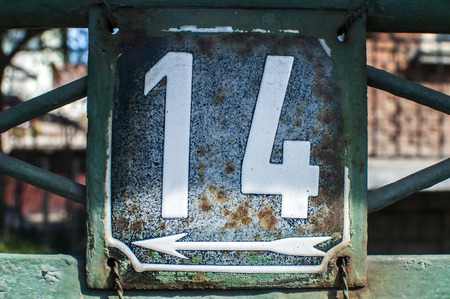 number 14: Weathered grunge square metal enameled plate of number of street address with number 14 closeup