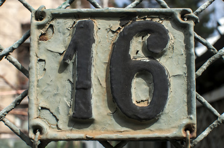 number 16: Old retro weathered painted cast iron plate with number 16 Stock Photo