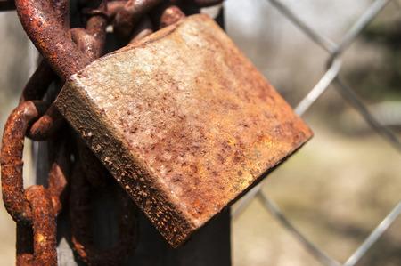 oxidize: Weathered grunge rusty closed padlock and metal chain closeup