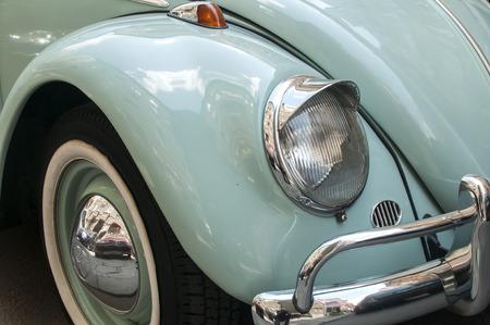 fender: Front fender and headlight of blue vintage car detail closeup