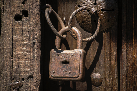 Old weathered grunge rusty locked padlock with rings on old wooden board door