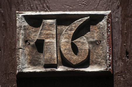 number 16: Old retro weathered carved wooden home plate with number 16