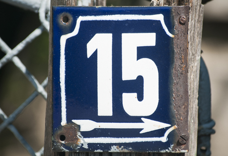enameled: Weathered grunge square metal enameled plate of number of street address with number 15 closeup Stock Photo
