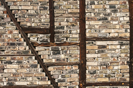 strengthening: Old weathered grunge brick wall with wooden frame-build strengthening as background Stock Photo