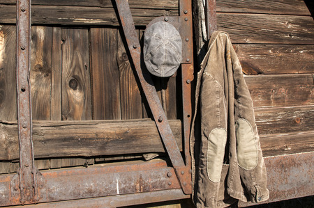 corduroy: Vintage corduroy male jacket and cap hanging on the wall of old wooden railway wagon as background