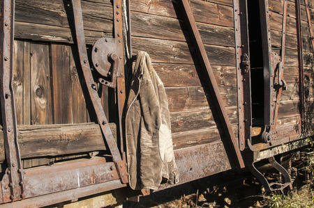 wood railways: Vintage corduroy male jacket hanging on the wall of old wooden railway wagon as background