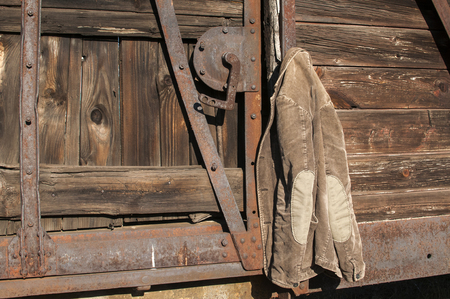 corduroy: Vintage corduroy male jacket hanging on the wall of old wooden railway wagon as background
